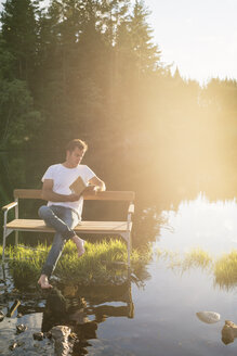Man sitting on bench in middle of lake - FOLF05587