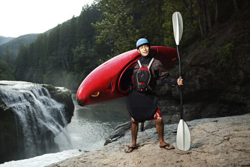 Portrait of confident kayaker standing on rock with waterfall and trees in background - CAVF31246