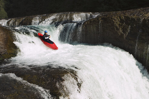 Kayaker paddling through waterfall - CAVF31249