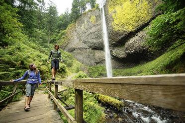 Couple walking on footbridge by waterfall in forest - CAVF31255