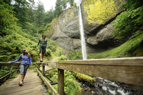 Couple walking on footbridge by waterfall in forest - CAVF31255