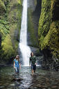 Couple standing in stream against waterfall - CAVF31261