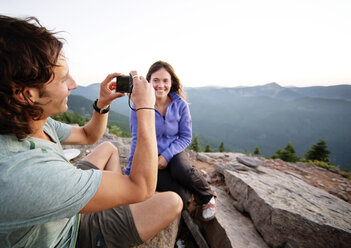Woman looking at boyfriend photographing while sitting on mountain - CAVF31270