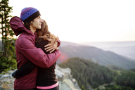 Couple embracing while standing on top of mountain against clear sky - CAVF31273