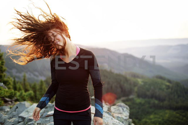 Happy woman shaking head while standing on cliff against clear sky - CAVF31276