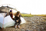 Happy couple relaxing in tent against clear sky - CAVF31279
