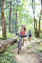 Couple riding bicycle on dirt road in forest - CAVF31282
