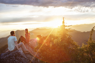 Happy couple sitting on mountain against cloudy sky during sunset - CAVF31291