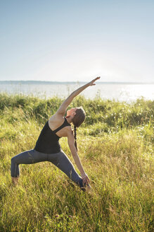 Woman practicing extended side angle pose yoga on grassy field by sea during sunny day - CAVF31297
