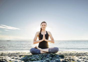 Woman meditating in lotus position at beach against sky - CAVF31306