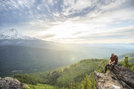 High angle view of hiker looking at view while sitting on mountain against cloudy sky - CAVF31330