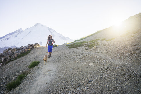 Female hiker with dog walking on mountain against clear sky during sunny day - CAVF31345