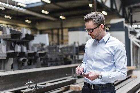 Man using tablet on factory shop floor - DIGF03548