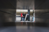 Two men with clipboard talking on factory shop floor - DIGF03557