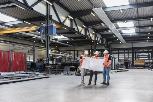 Three men wearing hard hats and safety vests looking at plan on factory shop floor - DIGF03578