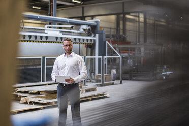 Businessman using tablet on factory shop floor - DIGF03584