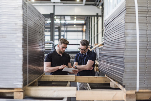 Two men using tablet in factory - DIGF03587