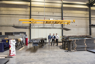 Three men standing on factory shop floor - DIGF03590