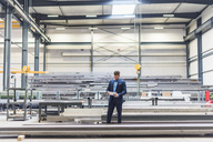 Businessman with tablet standing on factory shop floor - DIGF03632