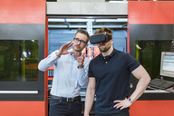 Man explaining machine to colleague wearing VR glasses in factory - DIGF03641