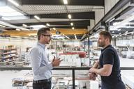 Two men talking on factory shop floor - DIGF03644