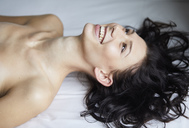 Laughing dark-haired young woman lying on bed - PNEF00568