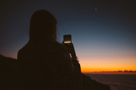 Rear view of woman photographing sunset through smart phone - CAVF31383