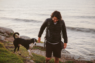 Male hiker walking with dog on rock by sea - CAVF31386