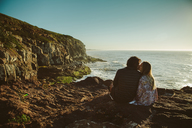 Rear view of couple kissing while sitting on rock by sea against clear sky - CAVF31392