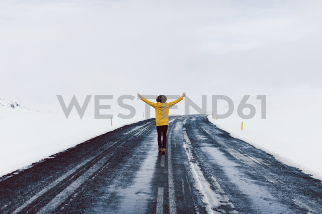 Rear view of man with arms outstretched standing on highway amidst snow field against sky - CAVF31404 - Cavan Images/Westend61