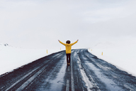 Rear view of man with arms outstretched standing on highway amidst snow field against sky - CAVF31404