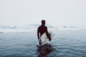 Man carrying surfboard while standing in icy sea against clear sky during winter - CAVF31407