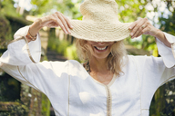 Happy woman wearing straw hat at park - CAVF31482