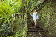 Thoughtful sensuous woman standing on mossy steps in forest - CAVF31491