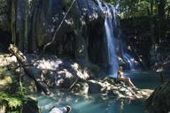 Woman sitting on rock by waterfall - CAVF31506