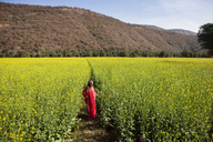 Woman standing amidst oilseed rape field - CAVF31509