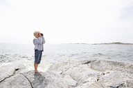 Boy standing on rocky seashore and looking through binoculars in the Stockholm archipelago - FOLF05736