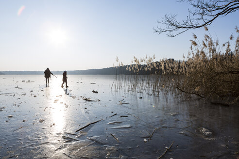 Germany, Brandenburg, Lake Straussee, frozen lake and silhouettes of two people walking on ice - OJF00247