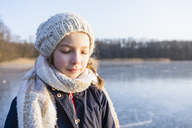 Germany, Brandenburg, Lake Straussee, portrait of a girl standing on frozen lake, eyes closed - OJF00253