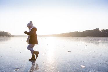 Germany, Brandenburg, Lake Straussee, girl walking on frozen lake - OJF00256