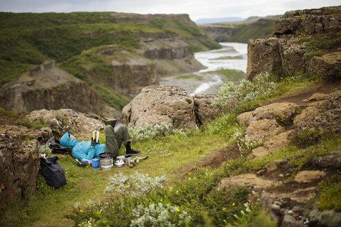 Tourist lying on edge of Hvita river canyon and reading - FOLF05862