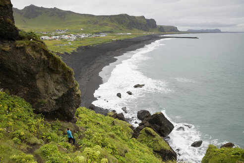 Hiker looking from cliff at black sand beach in Iceland - FOLF05868