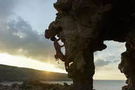 Side view of man climbing rock formation against cloudy sky during sunset - CAVF31619