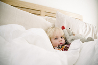 Portrait of cute boy with stuffed toy relaxing on bed at home - CAVF31652