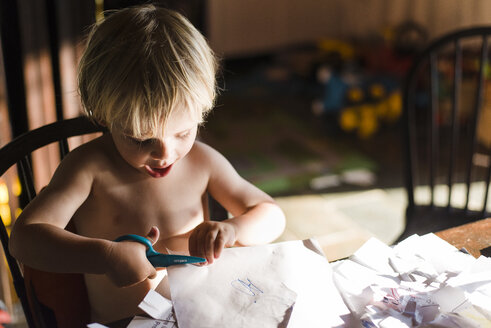 High angle view of shirtless boy cutting papers with scissors while sitting on chair at home - CAVF31655