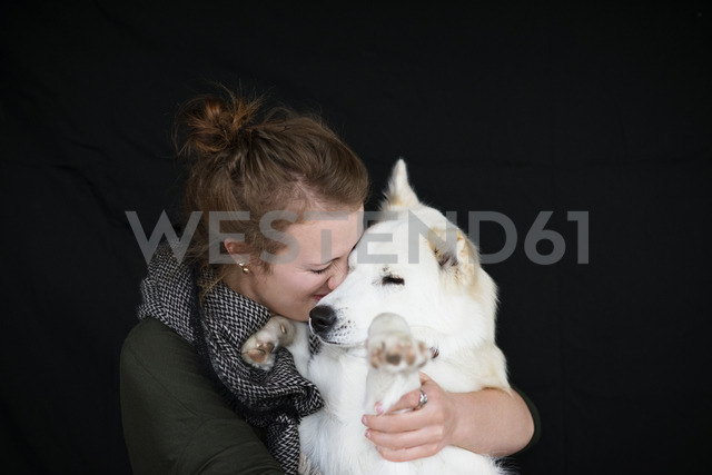 Happy woman holding dog against black background - CAVF31697