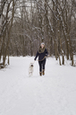 Happy woman walking with dog on snow covered field against bare trees - CAVF31700
