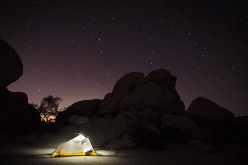 Illuminated tent by rock formation against starry sky - CAVF31709