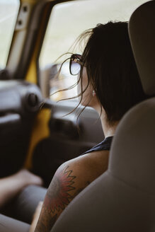 Young woman with tattoo on shoulder sitting in off-road vehicle - CAVF31724