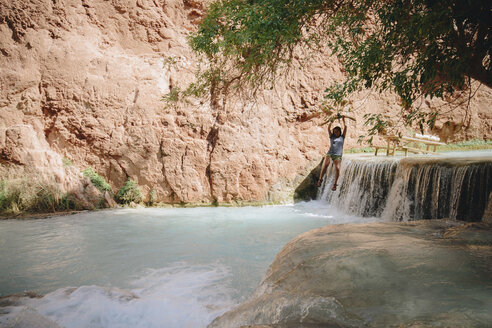 Playful woman hanging on tree against waterfall - CAVF31733